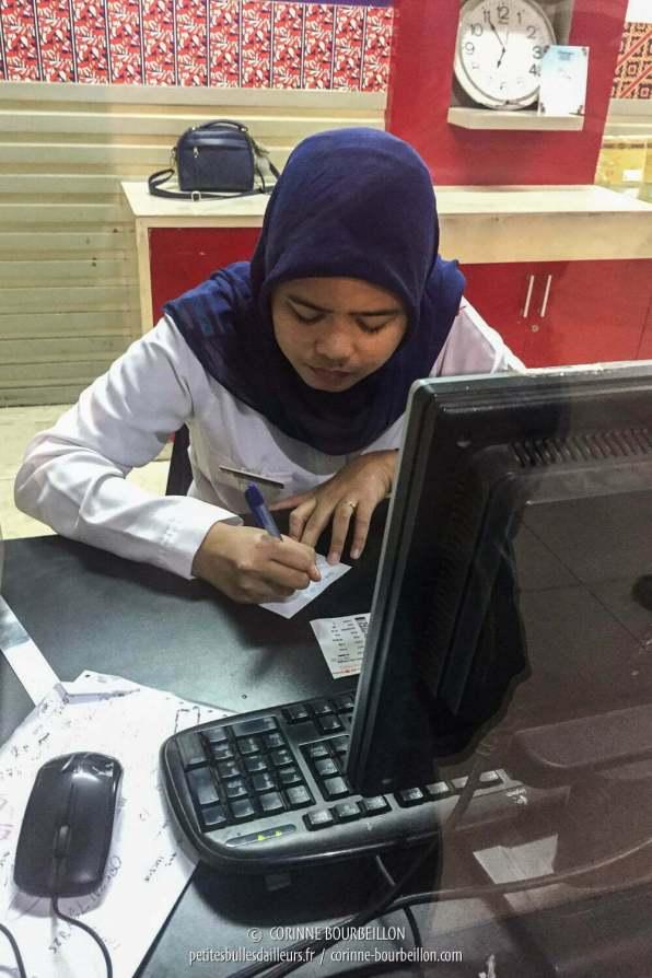 Au bureau Lion Air, la jeune femme m'écrit noir sur blanc les horaires du vol du lendemain. (Makassar, Sulawesi, Indonésie, juillet 2017)
