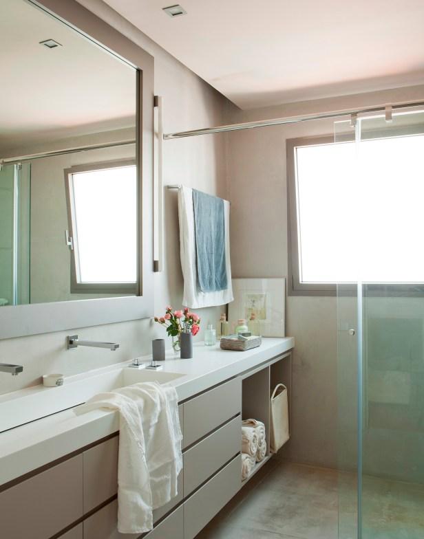 Combinação das cores branco + cinza. A bancada invade a área molhada, gostei do compartimento para alcançar as toalhas.