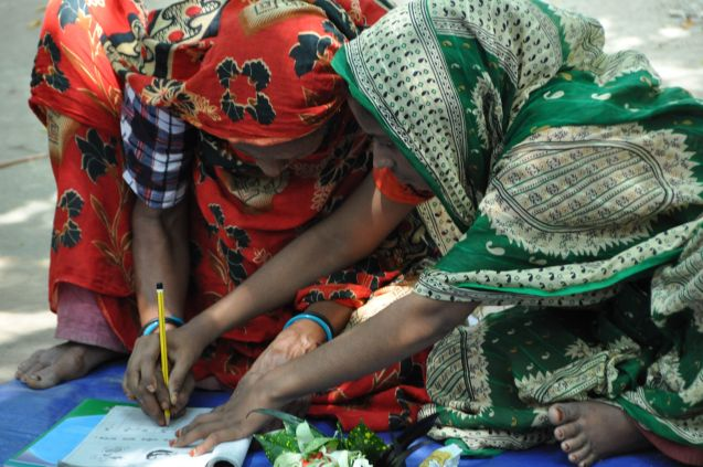 Young woman help elder woman to hold a pencil and write