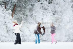 Nuoret aikuiset leikkivät lumella