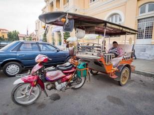 Tuktuk, výborný prostředek pro přepravu na kratší vzdálenosti, ale dali jsme s ním během dne i 2x 80 km. Tento je v Phnom Penhu, majitel čeká na rito. Narozdíl od Thajska nebo Indie jsou tuktuky v Kambodži cosi jako motorky s návěsem...