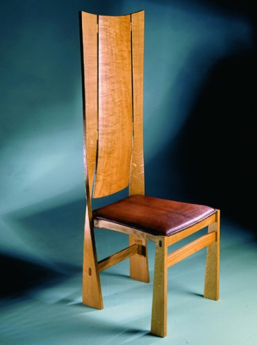 High back Twist Chair in steam bent oiled oak with sewn padded Russia leather seat.