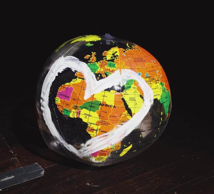 orange, green, and yellow globe on brown wooden surface