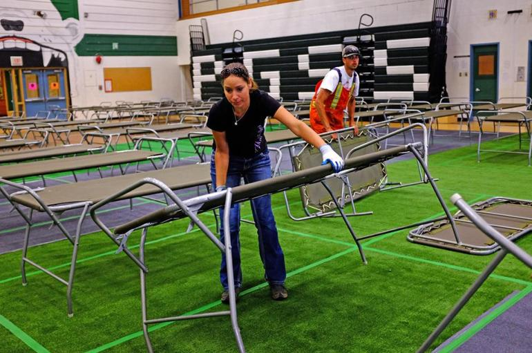Photo (top): Natisha Armstrong, City employee, unfolds and prepares one of the 180 beds now available at the PGSS gym in Prince George. City of Prince George photo