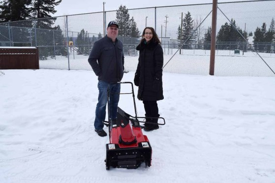 Dustin Lloyd of Cycle North presents one of three snowblowers the business is donating to local community associations to Heather Bromley of the West Bowl Community Association. Bill Phillips photo