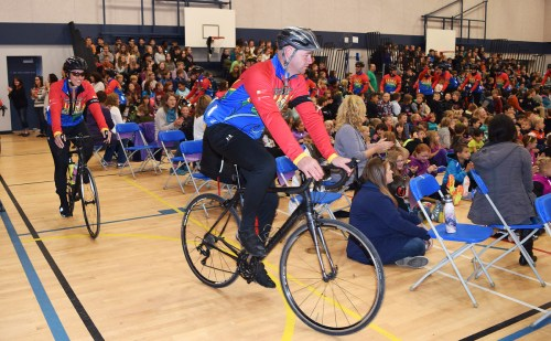 Cops for Cancer Tour de North riders are greeted during an assembly at Heather Park Elementary School Friday morning. Bill Phillips photo