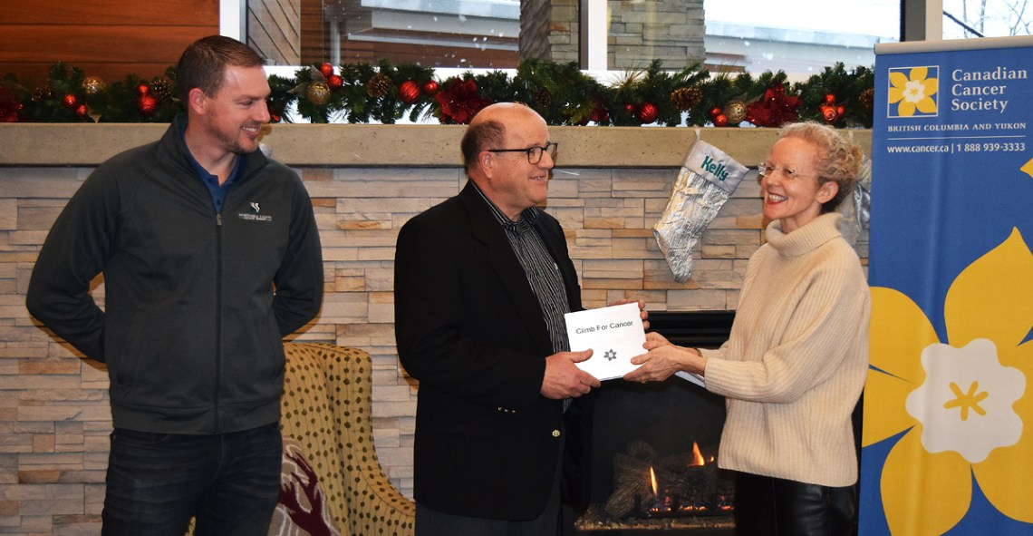 Margaret Jones-Bricker, of the Canadian Cancer Society, presents a recognition plaque to David Duck, Climb for Cancer campaign chair, and Doug Bell of Northern Lights Estate Winery. The Climb for Cancer has, so far, raised more than $100,000 for the Kordyban Lodge. Bill Phillips photo