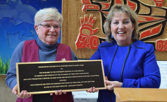 Northern Health board chair Colleen Nyce (right) presents a plaque to Lindy Steele, President of the Auxiliary to UHNBC, recognizing the 100th anniversary of the local auxiliary group. Bill Phillips photo