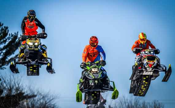 group of extreme lovers jumping on snowmobiles on sunny day