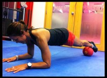 Woman works abs in plank position.