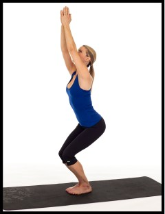 Woman practicing yoga chair pose.