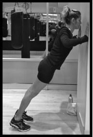 Woman doing a wall pushup.