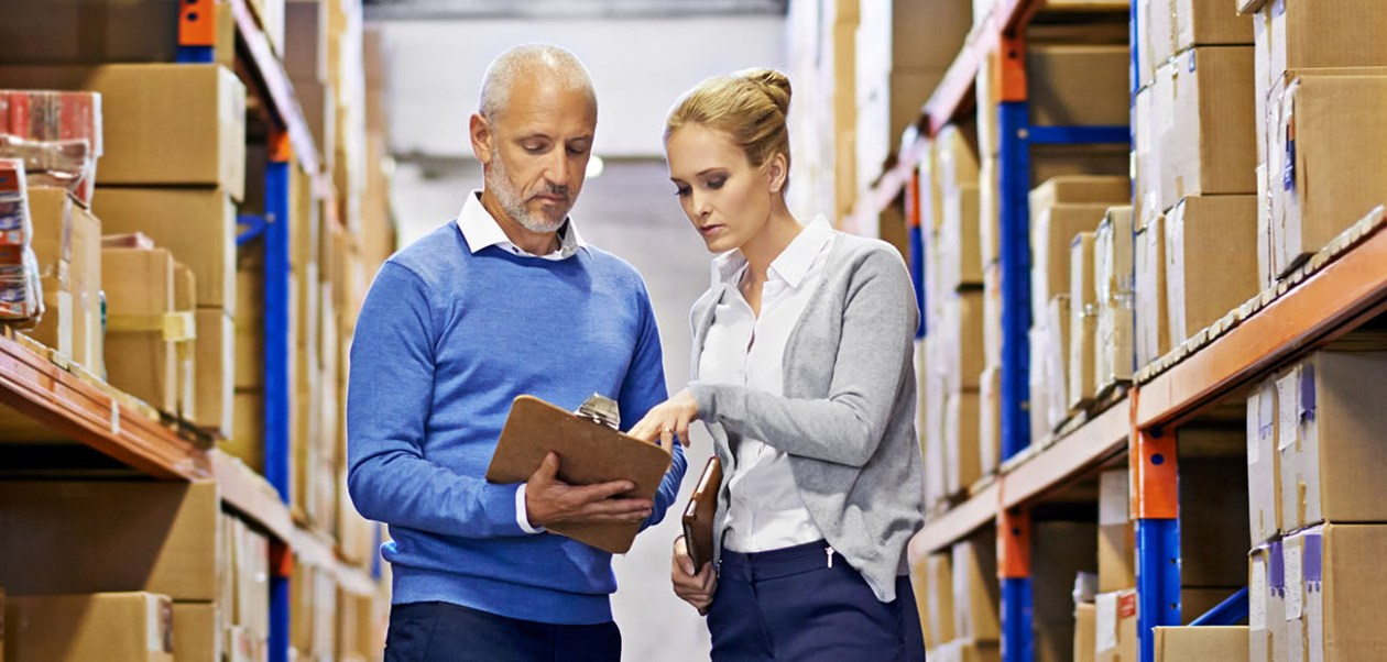 Shot of a man and woman inspecting inventory in a large distribution warehouse