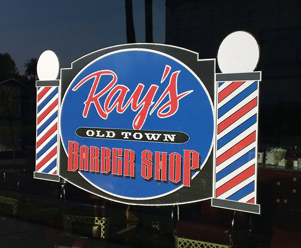 A digital print sign I designed and applied to the exterior window of Ray's Barber Shop