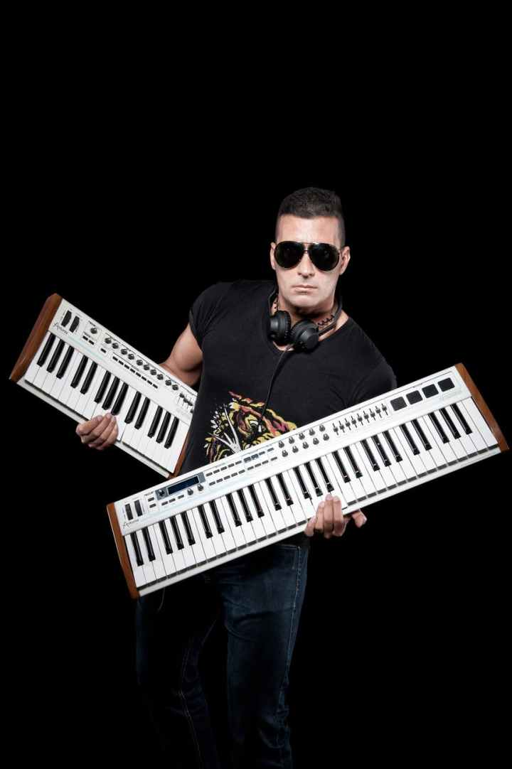 man wearing black crew neck shirt holding white keyboards