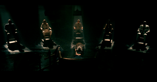 Five people sit in a darkened room under pools of light. They are tired to chairs with barbed wire.