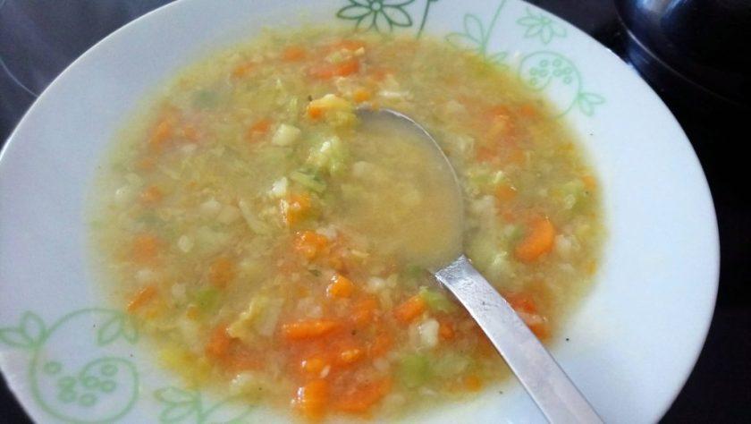 Ein Teller mit leckerer Gemüsesuppe. Ein Löffel liegt schon in der Suppe bereit. Wenn man auf das Bild klickt gelangt man zum eiweißarmen Rezept für Menschen mit PKU.
