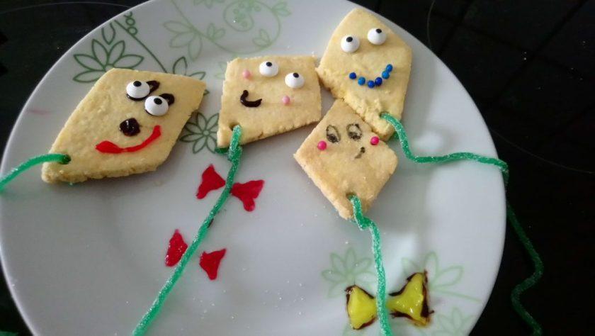 Auf einem Teller liegen vier rautenförmige Kekse die als kleine Flugdrachen dekoriert sind. Wenn man auf das Bild klickt gelangt man zum eiweißarmen Rezept für Menschen mit PKU.