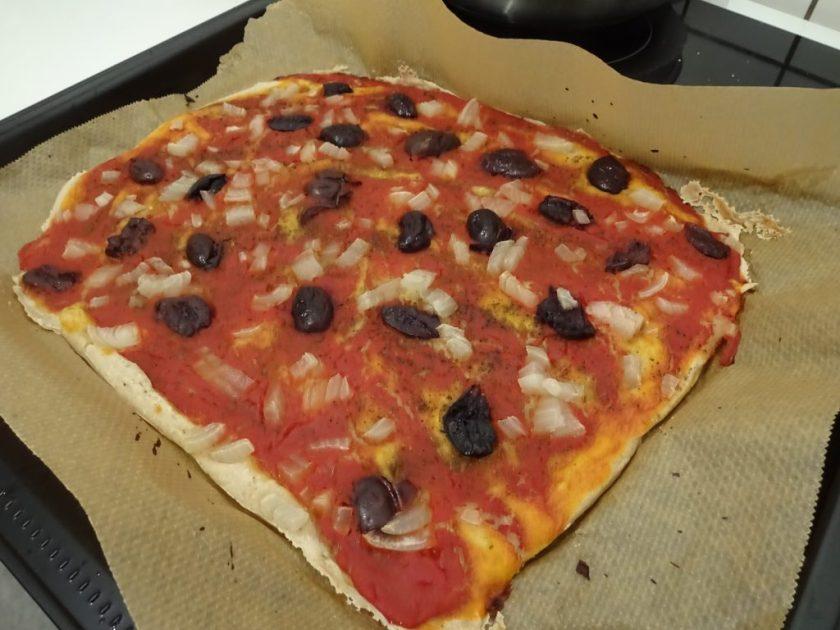 Ein Backblech mit einer Pizza darauf. Die Pizza hat Oliven und Zwiebeln als Belag. Wenn man auf das Bild klickt gelangt man zum eiweißarmen Rezept für Menschen mit PKU.