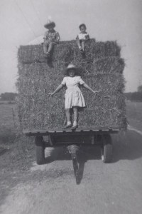 3 children riding on load of hay
