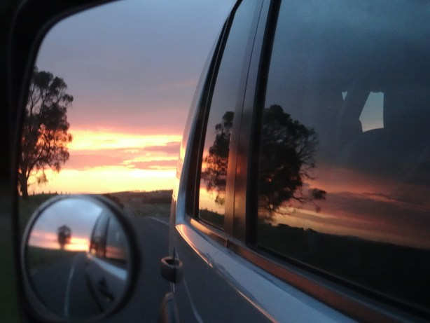 Passenger side mirror view of the sunset along the Great Ocean Road