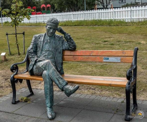 Statue d'un penseur assis sur un banc