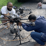 Two students working on a drone
