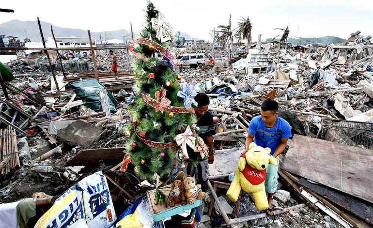 A typhoon survivor decorates a Christmas tree amid the rubble of destroyed houses in the City of Tacloban in central Philippines