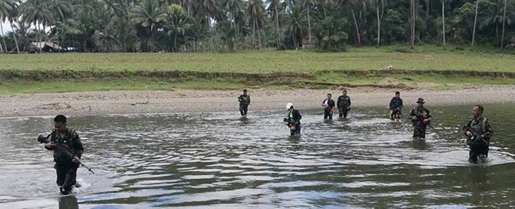 Soldiers wade through a river as they search for the hideout of Islamic militants in Inabanga town, Bohol province
