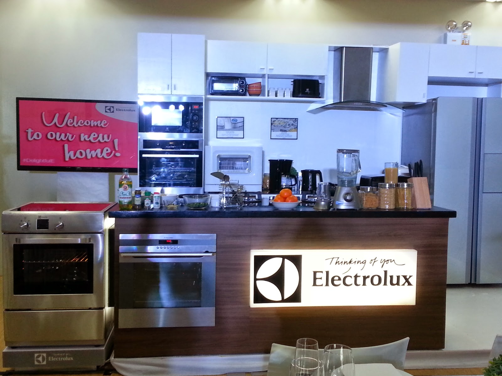 electrolux kitchen appliances. a dining table with plate settings and fully furnished kitchen! kudos to whoever transformed this corporate space into home, sweet home! electrolux kitchen appliances c