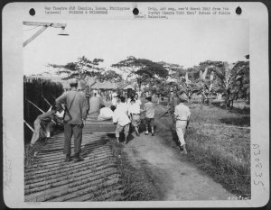 Members of 1st Cavalry-guard-Japanese-prisoners-burying-dead-at-STIC