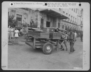 Elmer Mocklin and Charles Bradfield pushing cart with two caskets of internees killed in Japanese shelling of STIC, February 1945