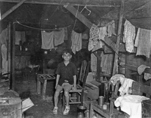 Young boy sits inside STIC shanty, 1945