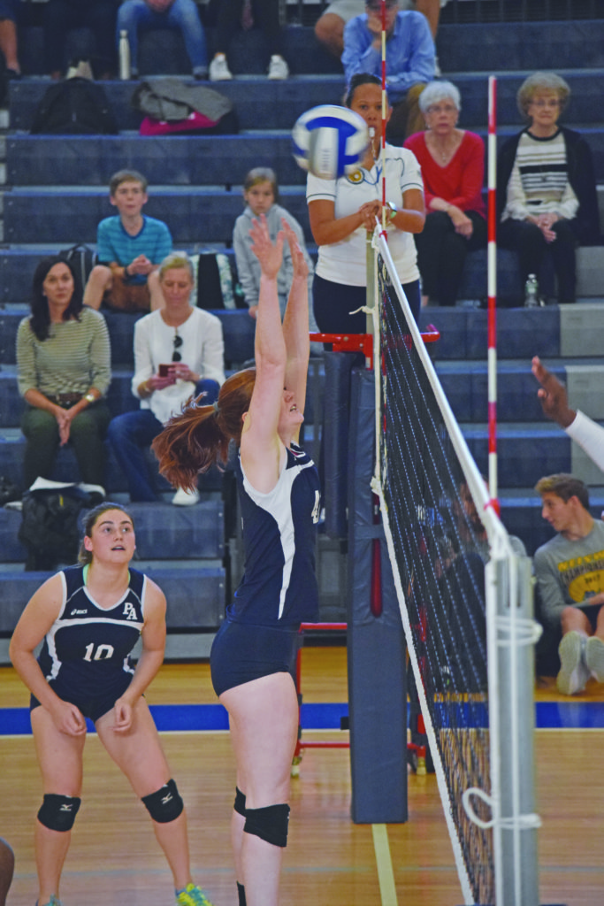 Co-Captain Claudia Leopold '18 jumps up to block at the net.