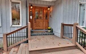 Welcoming entry with wood and stone leading up to it.
