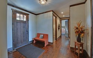Front entry with hardwood floors and a 3 pane stained front door.