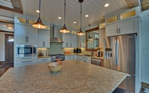 Spacious kitchen with white cabinets and granite countertops.