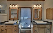 Master bath with dual vanities featuring raised square bowls on a granite top.