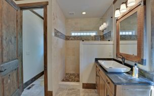 Lovely walk in tiled shower with a raised bowl vanity.