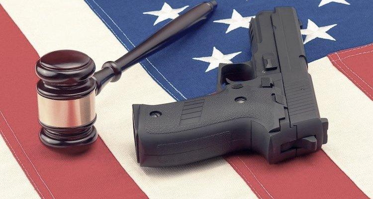 Gun and judge's hammer on American flag