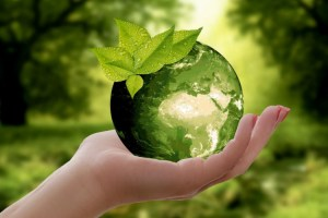 Womans holding green planet Earth with leaves