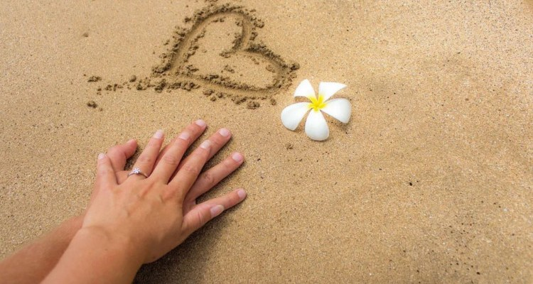 Heart on beach with flower and holding hands