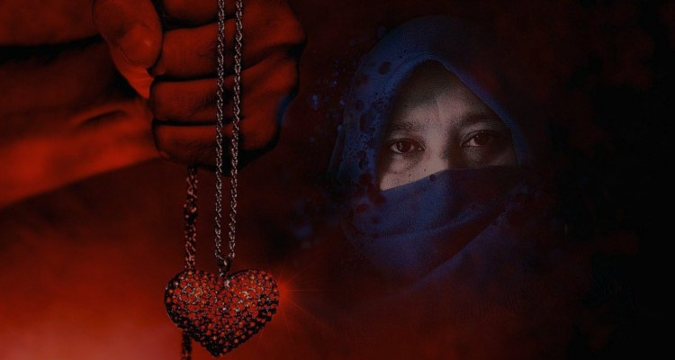 Man holding a heart necklace and muslim woman