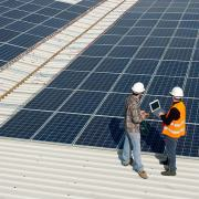 Men working on a photovoltaic plant with large electric panels