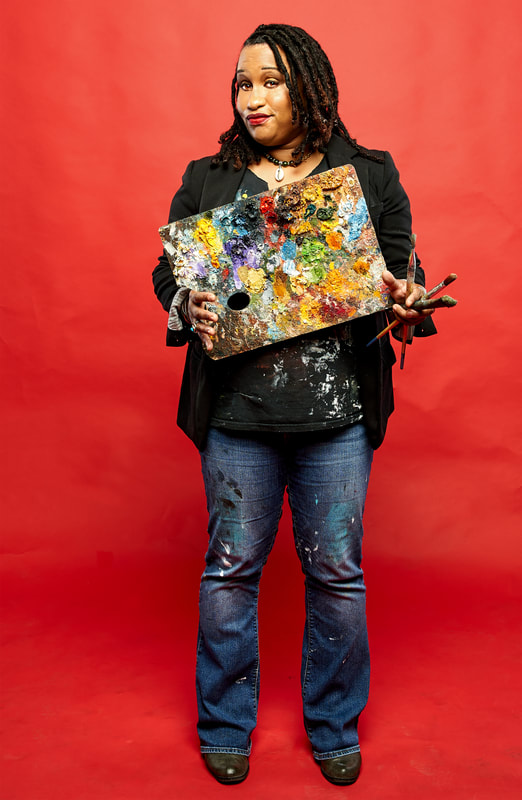A photograph of Keisha Whatley, a Black woman with braids who is holding a painting and is in front of a red background.