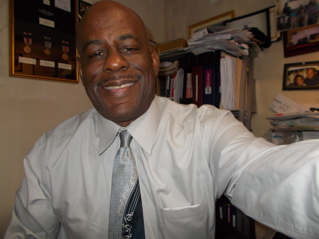 Michael Johnson from Drone Lecture. The photo is of a smiling man in a white shirt in front of a shelf of binders.