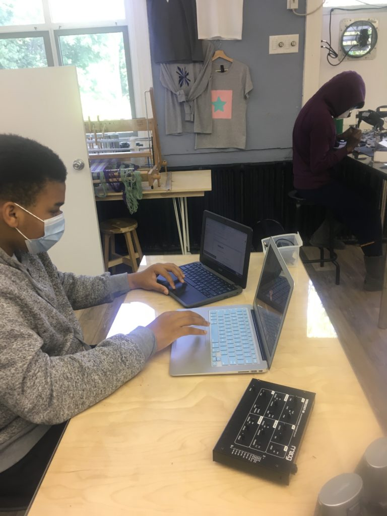 A student at The Crefeld School working in the CrEF Lab. He is at a table and has each hand on a different laptop in front of him.