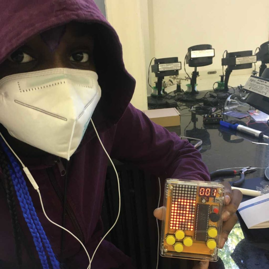 A student from The Crefeld School's CrEF Lab holding up his project. He is wearing a face mask and a hoodie.