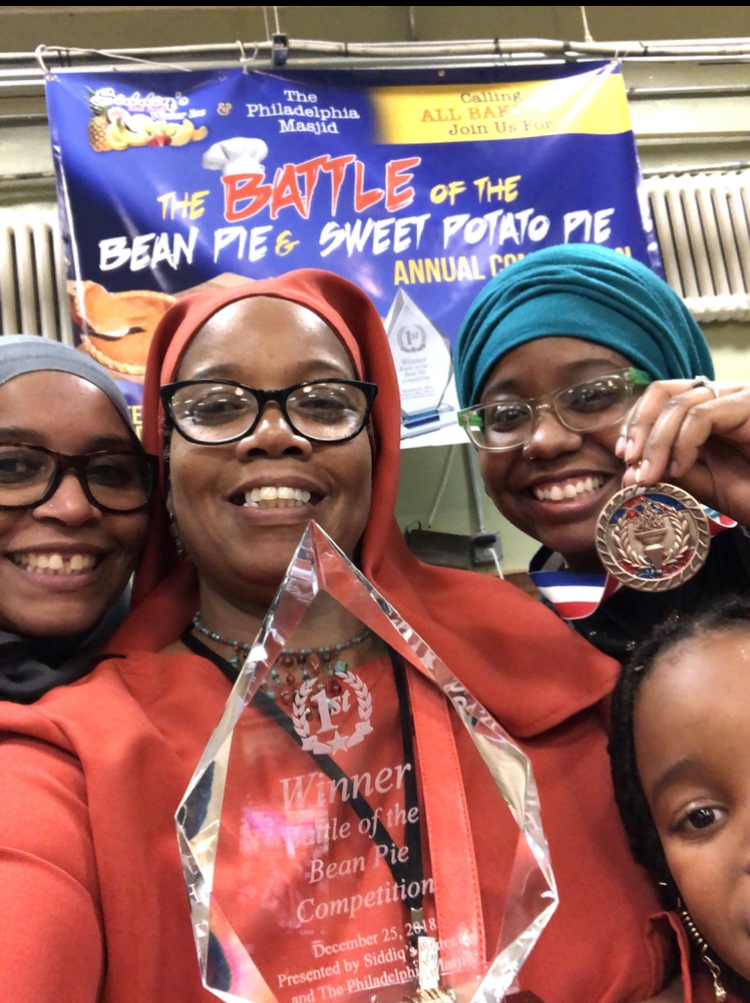 Nefertari Muhammad and her daughters of Sister's Original Supreme Pies. Nefertari is in red holding an award and is surrounded by her three daughters. All four of them are smiling widely.