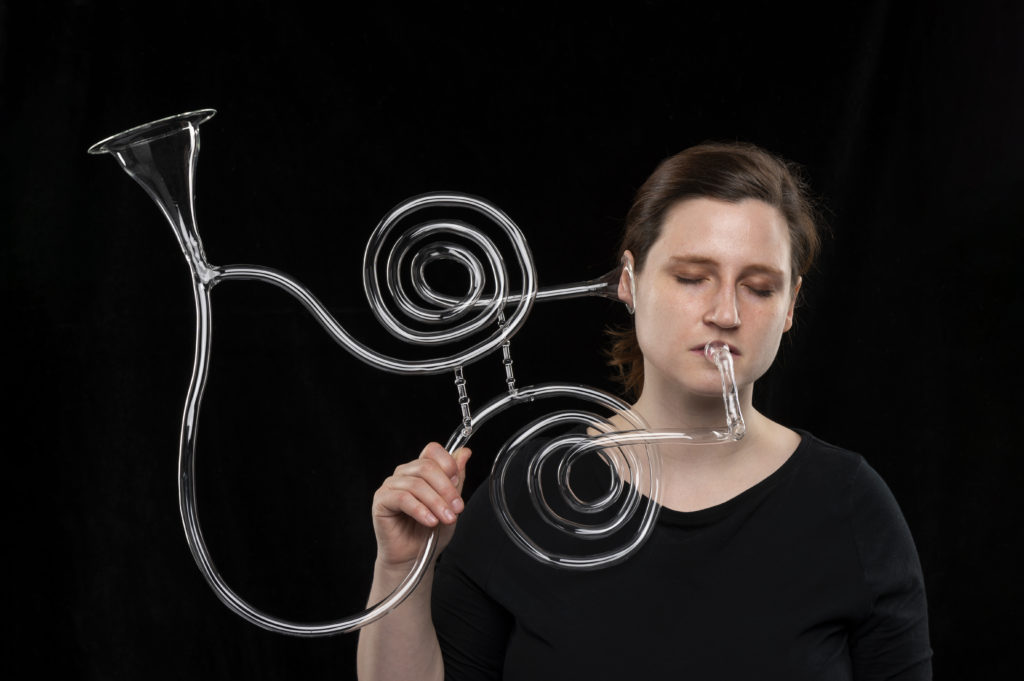 A photo of Madeline Rile Smith with her Deafening Trumpet. The picture features a woman holding a glass trumpet that is has two cones, one that goes directly in the woman's ear.
